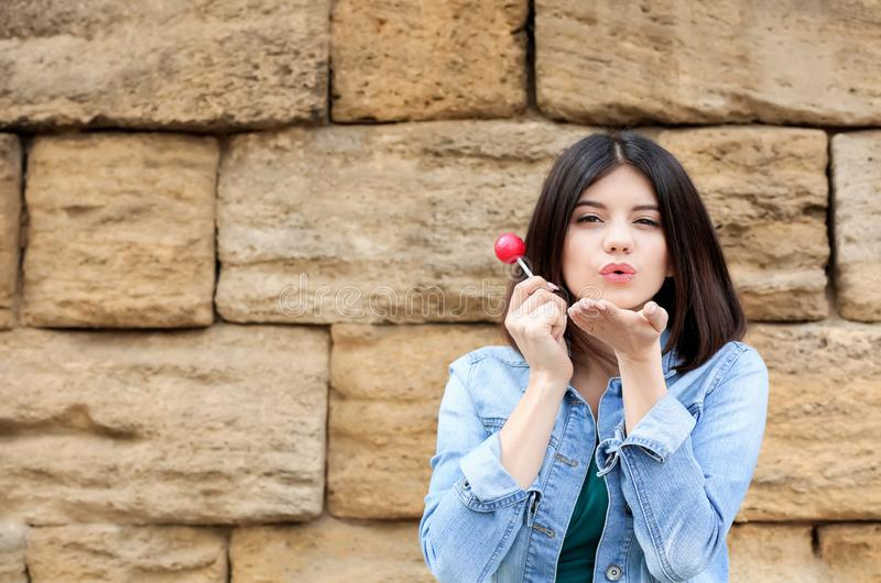 Beautiful young woman with lollipop blowing kiss against brick wall stock image