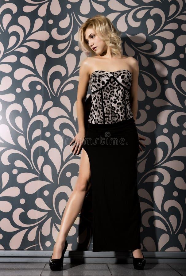 Beautiful young woman in a long black skirt posing near the wall stock photos