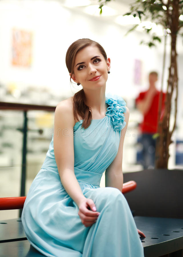 Beautiful young woman in a long blue dress in anticipation. Thoughtfully looking up stock image