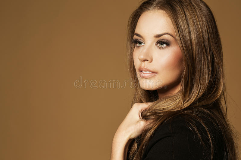 Beautiful young woman with long brown hair. Pretty model poses at studio stock photos