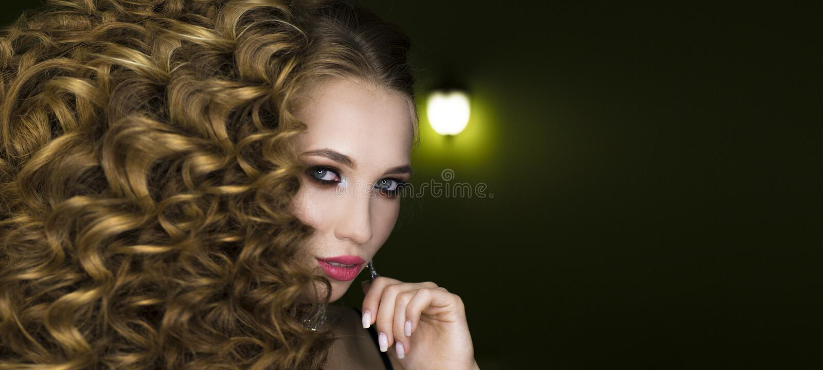 Beautiful young woman with long curly hairs royalty free stock images
