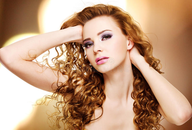 Beautiful young woman with long curly hairs stock images