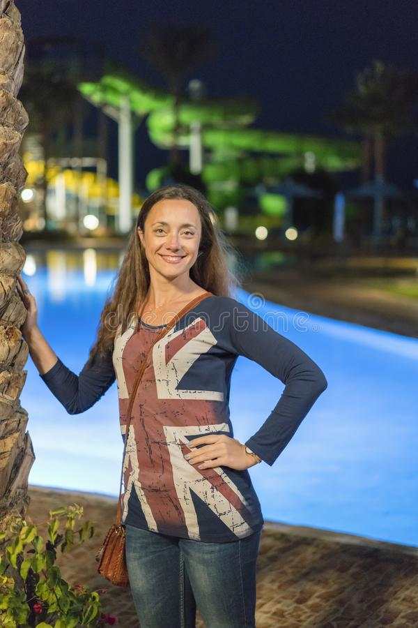 Beautiful young woman with long hair near the night pool. British flag. vertical photo royalty free stock image