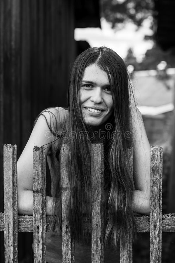 Beautiful young woman with long hair near a rustic wooden fence. stock photos
