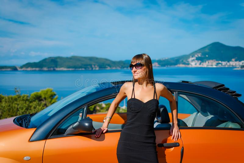 Beautiful young woman with long hair standing near orange cabriolet at the Mediterranean sea coast royalty free stock images