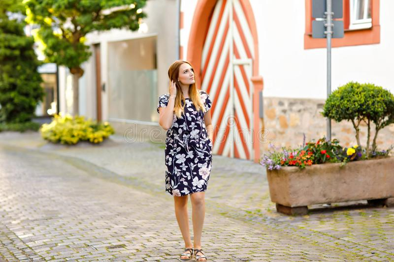 Beautiful young woman with long hairs in summer dress going for a walk in German city. Happy girl enjoying walking in stock photography