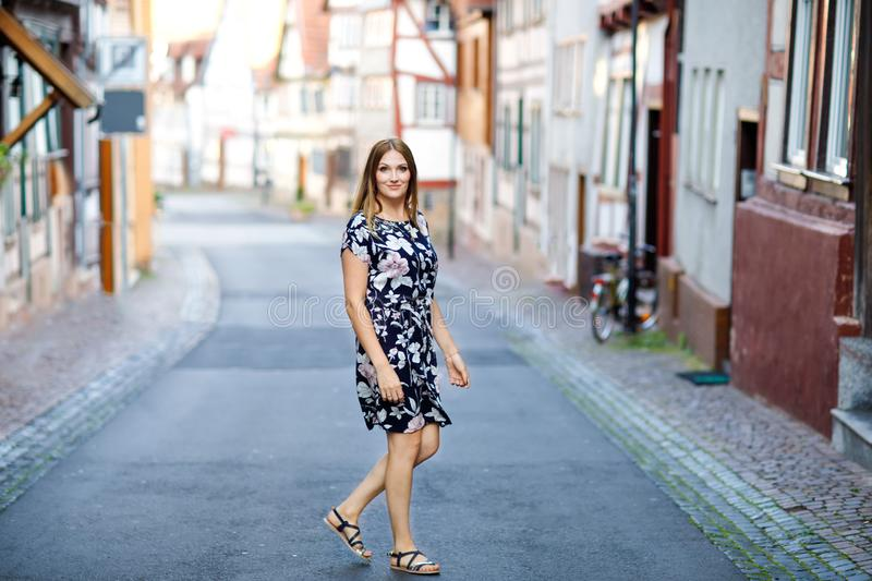 Beautiful young woman with long hairs in summer dress going for a walk in German city. Happy girl enjoying walking in royalty free stock image