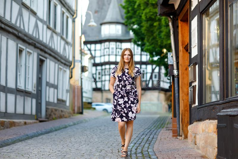 Beautiful young woman with long hairs in summer dress going for a walk in German city. Happy girl enjoying walking in royalty free stock images