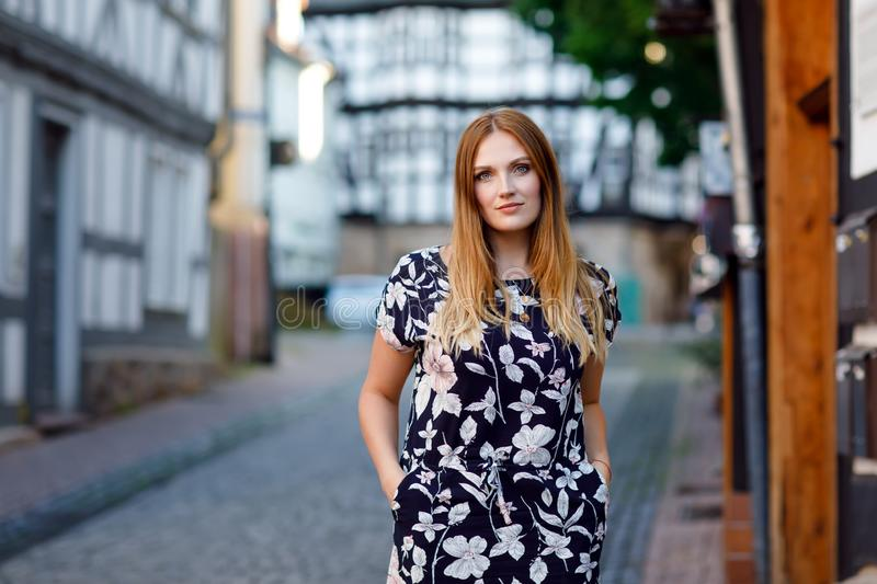 Beautiful young woman with long hairs in summer dress going for a walk in German city. Happy girl enjoying walking in stock photo