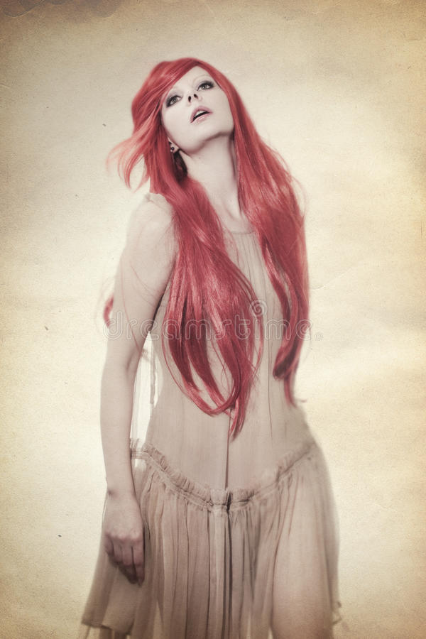Beautiful young woman. Beautiful woman with long red hair dancing, studio shot royalty free stock photos