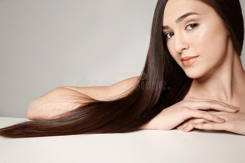 Beautiful young woman with long straight hair. On light background royalty free stock photo
