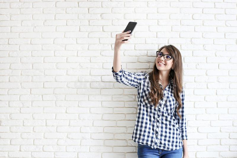 Stylish woman making selfie with shopping bag on the yellow wall background. Winter holiday sale stock photos
