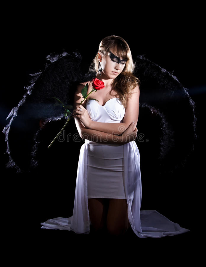 Beautiful young woman in a long white dress and with black wings royalty free stock image