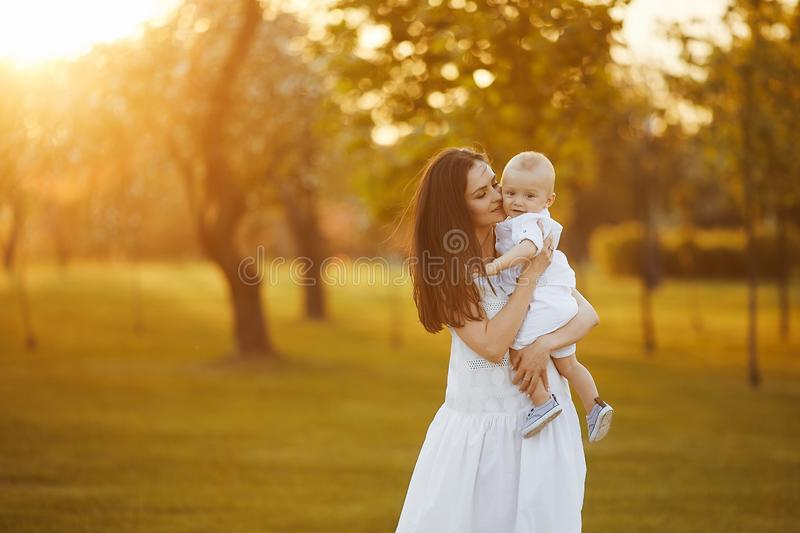 Beautiful young woman in a long white dress with a cute little baby boy in shirt and shorts on her hands posing at the royalty free stock image