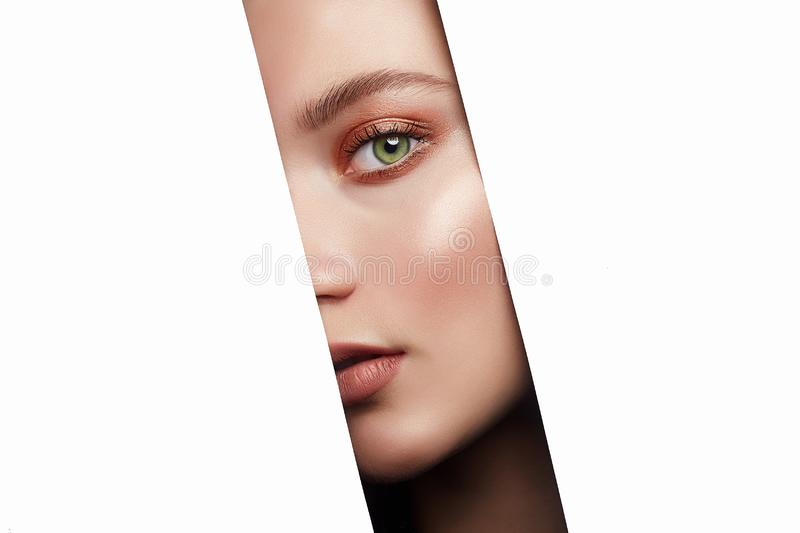 Beautiful young woman looking at camera through hole on white stock photo