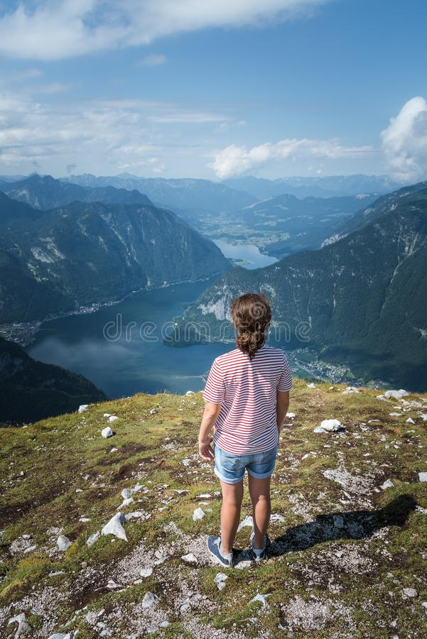 Beautiful young woman looking at the lake in the mountains royalty free stock image