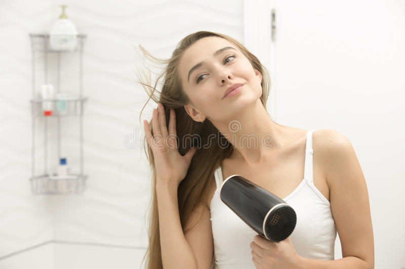 Beautiful young woman looking at the mirror drying hair royalty free stock photos