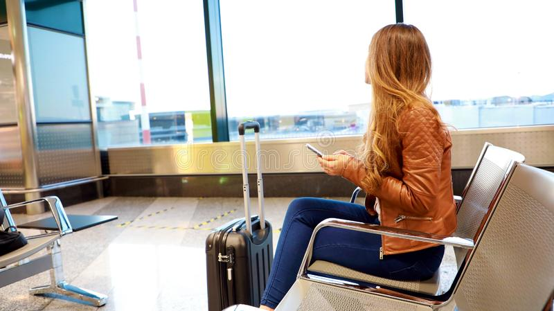 Beautiful young woman looking out window at flying airplane while waiting boarding on aircraft in airport lounge royalty free stock image