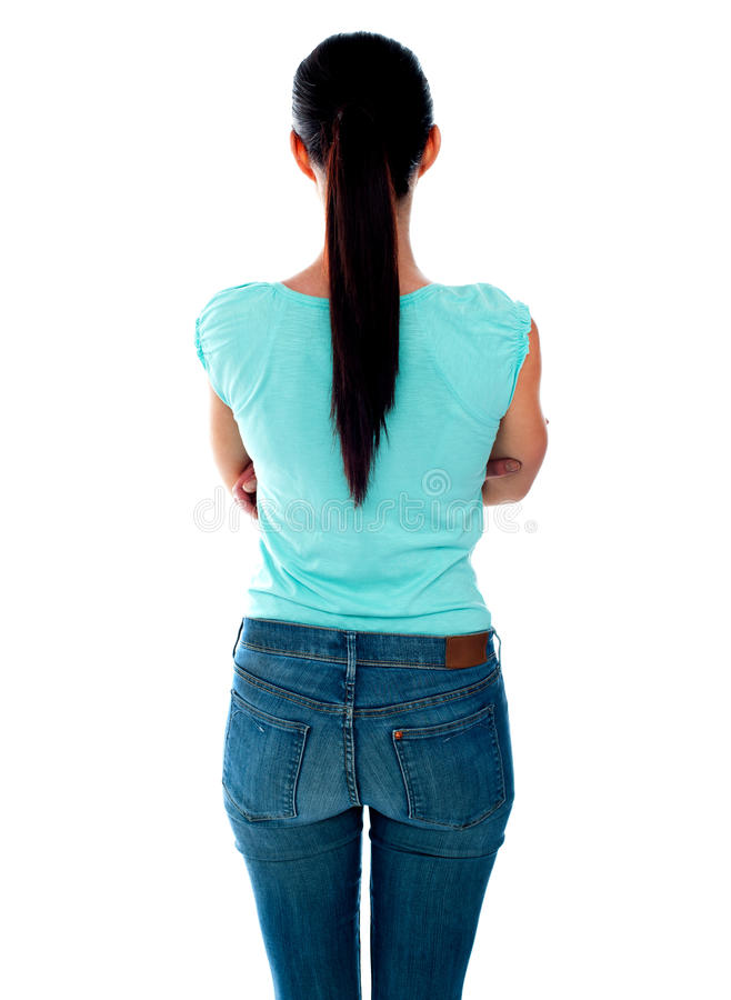 Beautiful young woman looking at wall. Rear view royalty free stock photos