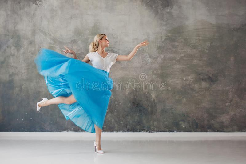 Beautiful young woman in a lush blue skirt, whirling and dancing. Summer style. Girl pointing to the right stock image