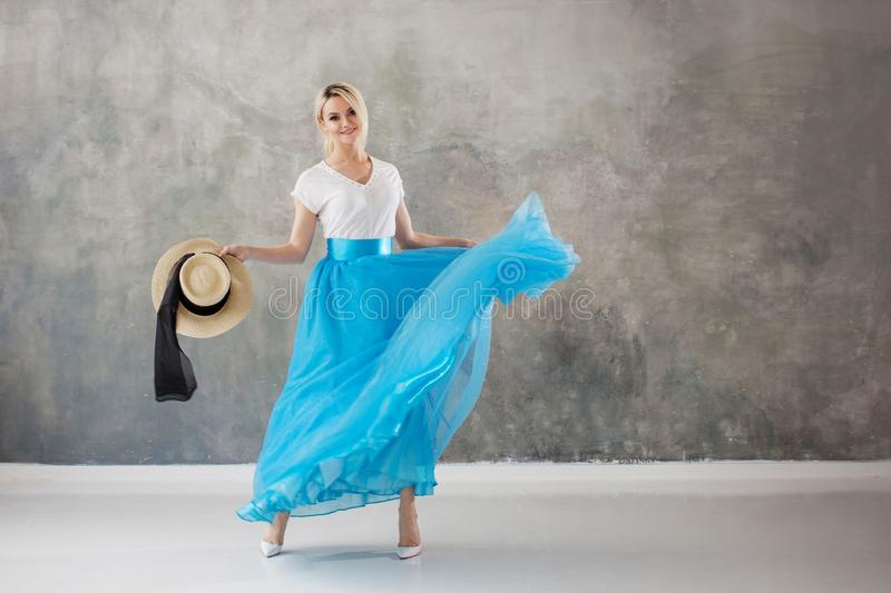 Beautiful young woman in a lush blue skirt, whirling and dancing. Summer style, straw hat with black ribbon. Grey textured background stock photo