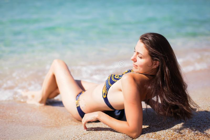 Beautiful young woman lying on the beach next to the blue sea.  stock photos