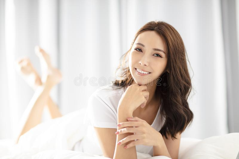 Young woman lying on the bed and smiling stock photos