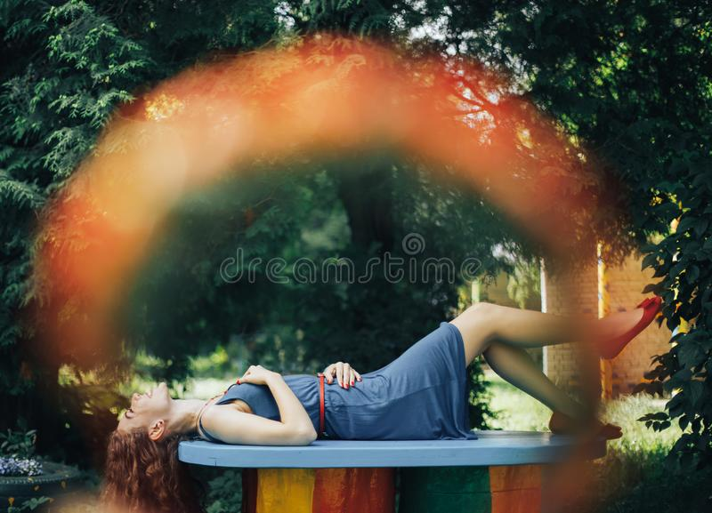 Beautiful young woman lying on a bench in a park with flowering trees royalty free stock images