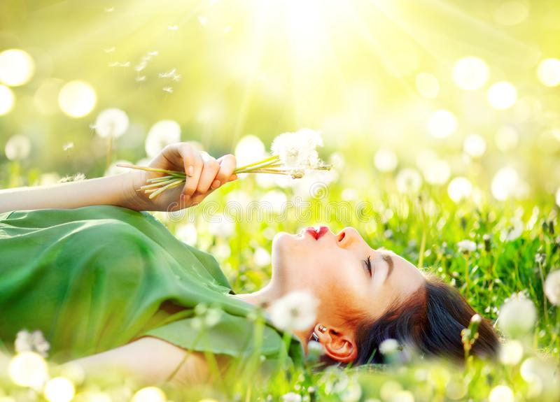 Beautiful young woman lying on the field in green grass and blowing dandelion flowers royalty free stock photography