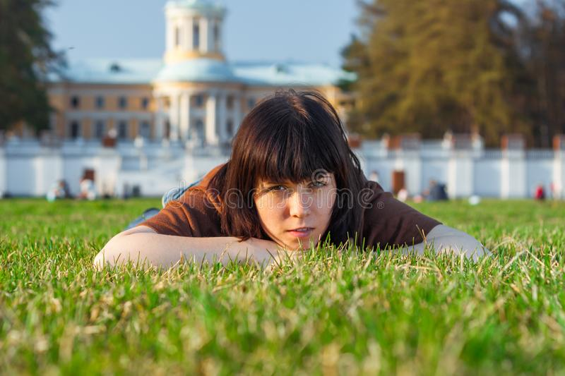 Beautiful Young Woman lying on a field, green grass. Outdoors Enjoy Nature. stock photography