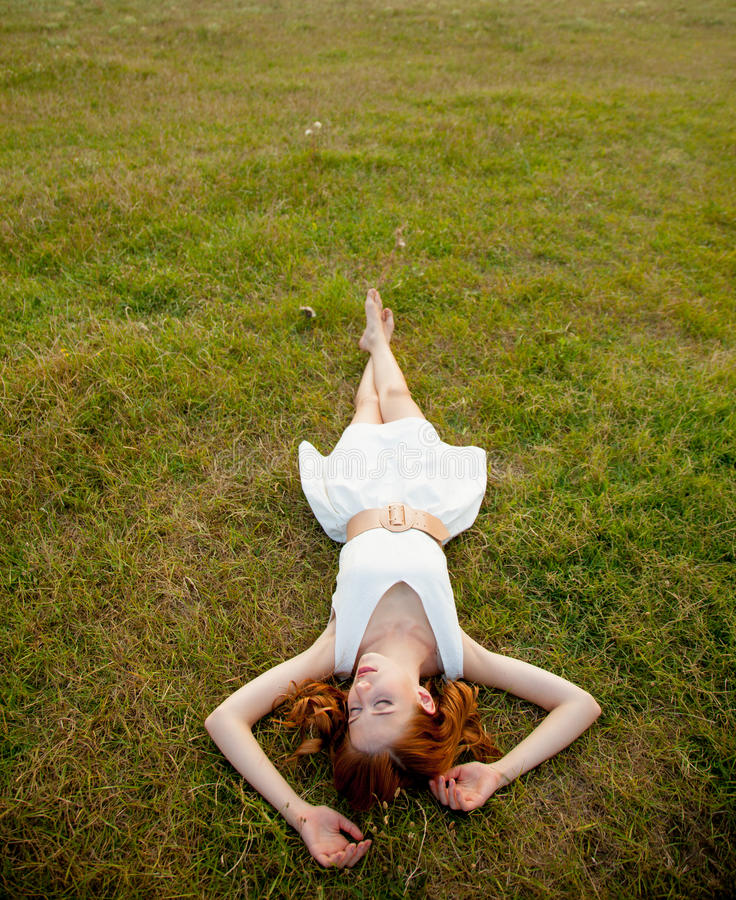 beautiful young woman lying in the field and relaxing stock photos