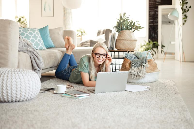 Happy young woman relaxing at home and using laptop royalty free stock photo