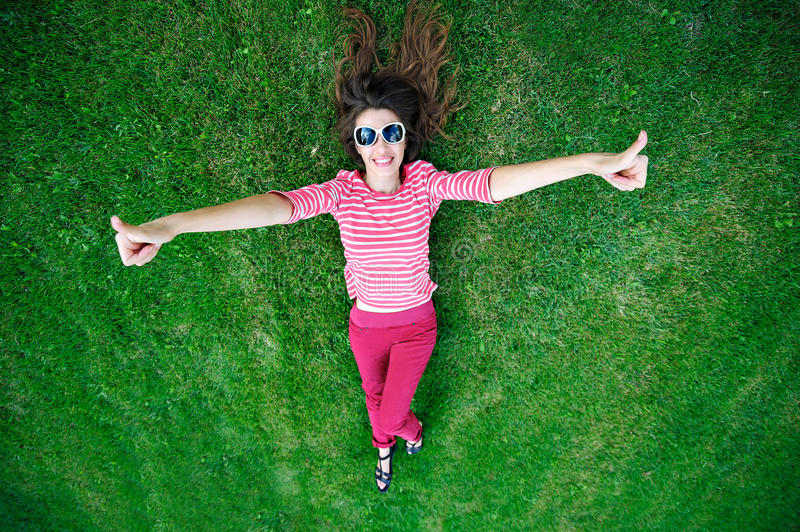 Beautiful young woman lying on the green grass in the Meadow.  royalty free stock photos