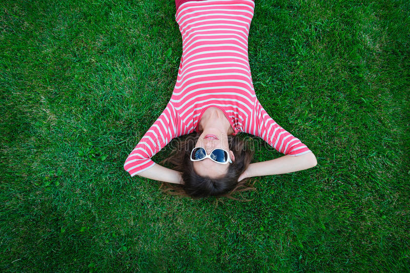 Beautiful young woman lying on the green grass in the Meadow.  royalty free stock image