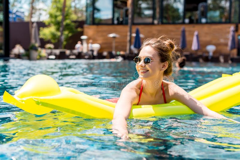 beautiful young woman lying on inflatable mattress in swimming pool royalty free stock image