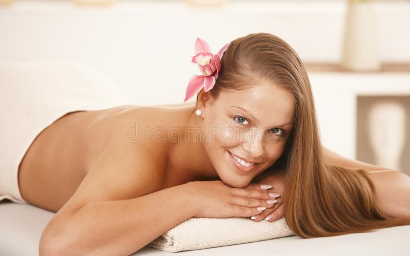 Beautiful young woman lying on massage bed stock photography