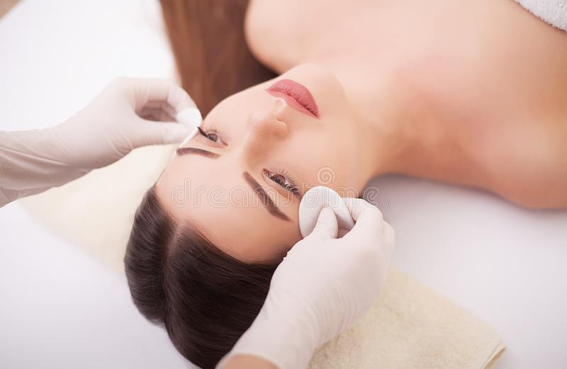 Beautiful young woman lying relaxed in a spa salon and receiving facial massage royalty free stock photography