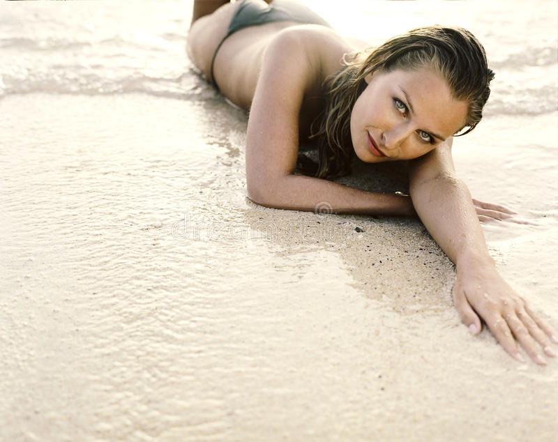 Beautiful young woman lying on the sand