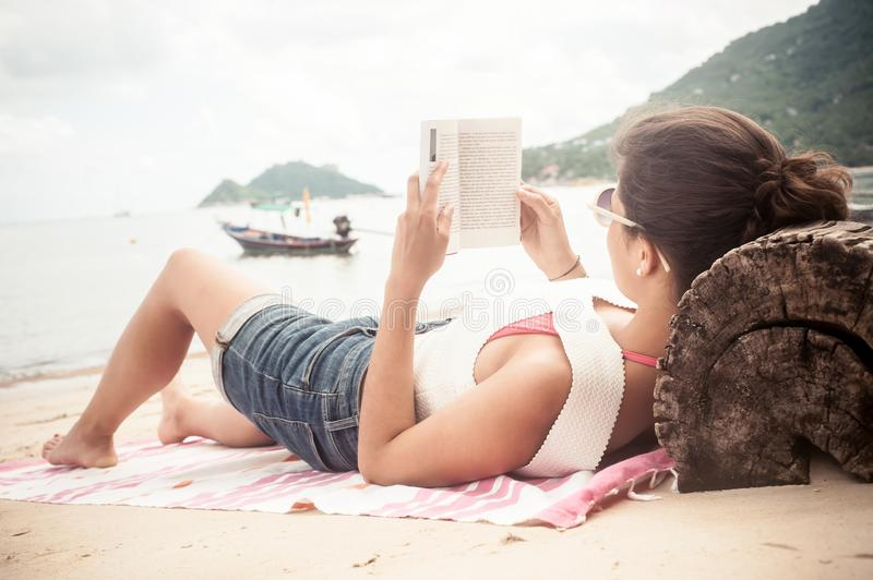 Beautiful young woman lying on tropical beach, reading books. Koh Tao, Thailand stock photography