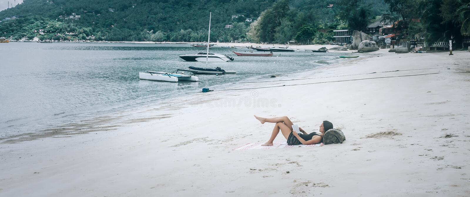 Beautiful young woman lying on tropical beach, reading books. Koh Tao, Thailand royalty free stock photo