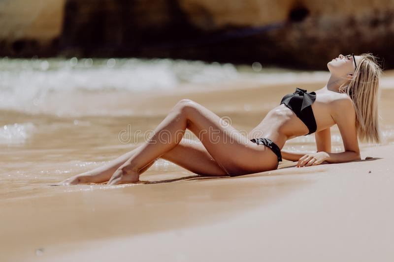 Beautiful young woman lying on the wet sand against ocean and blue sky royalty free stock photography