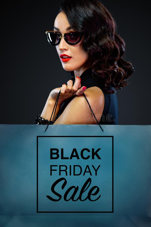 Closeup portrait of black friday sale concept for shop. Woman in sunglasses holding big bag  on dark background. Beautiful young woman make shopping in black royalty free stock image