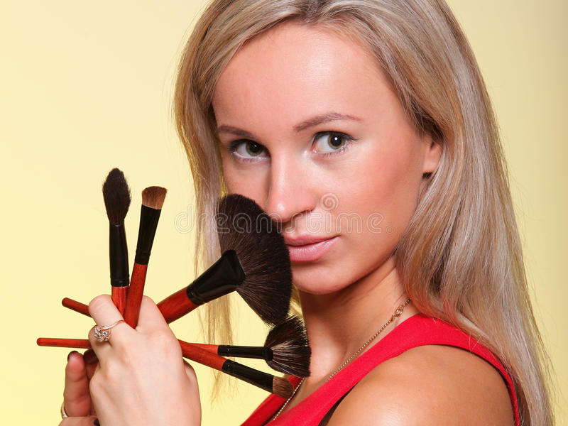 Beautiful young woman make-up brush yellow. Portrait of a young woman with long hair on yellow background making beauty face and hair style. Smile happy girl stock photo