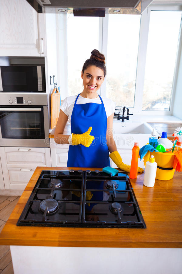 Beautiful young woman makes cleaning the house. Girl cleaning kitchen. Set. stock photography