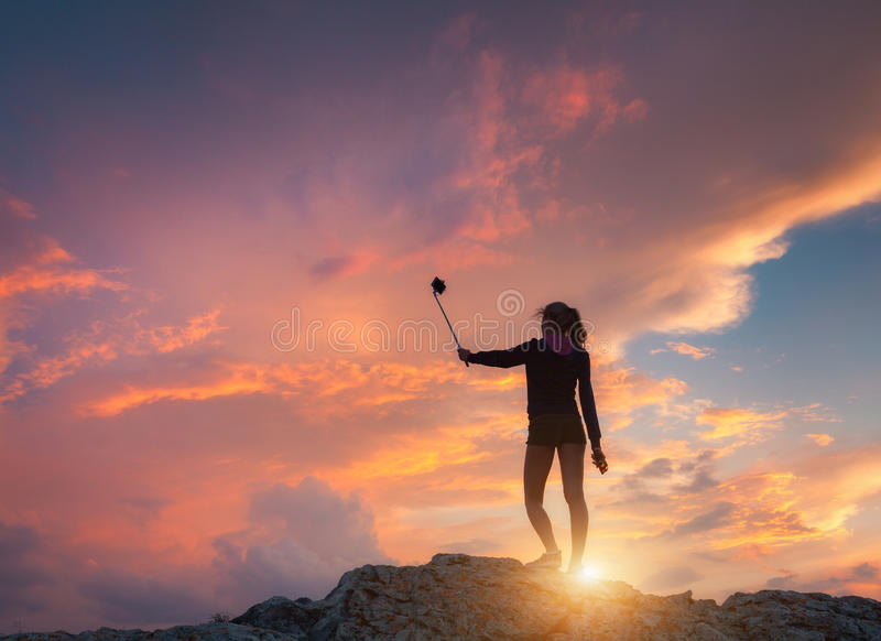 Beautiful young woman makes selfie for Instagram at sunset. Landscape with girl is photographing herself on the mountain peak against colorful sky with orange stock images