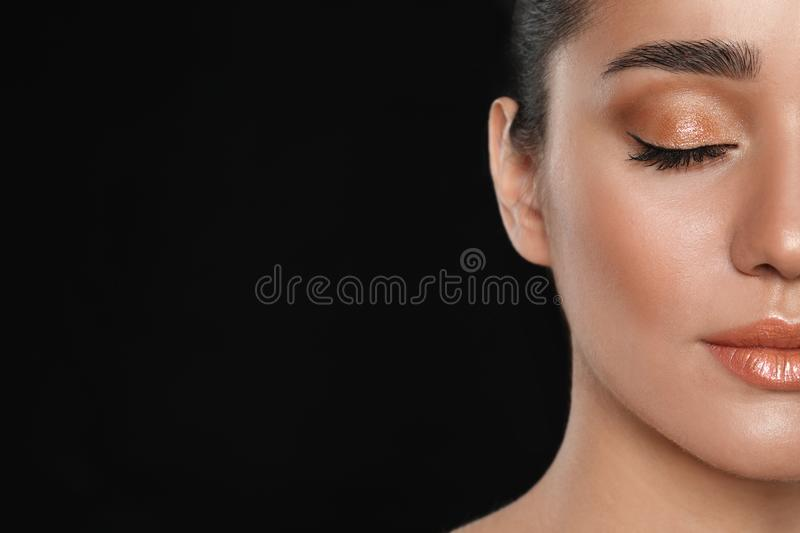 Beautiful young woman with  makeup on black background, closeup view. Space for text royalty free stock photos