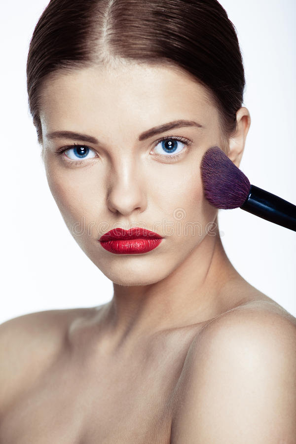 Beautiful young woman with a makeup brush. royalty free stock photography
