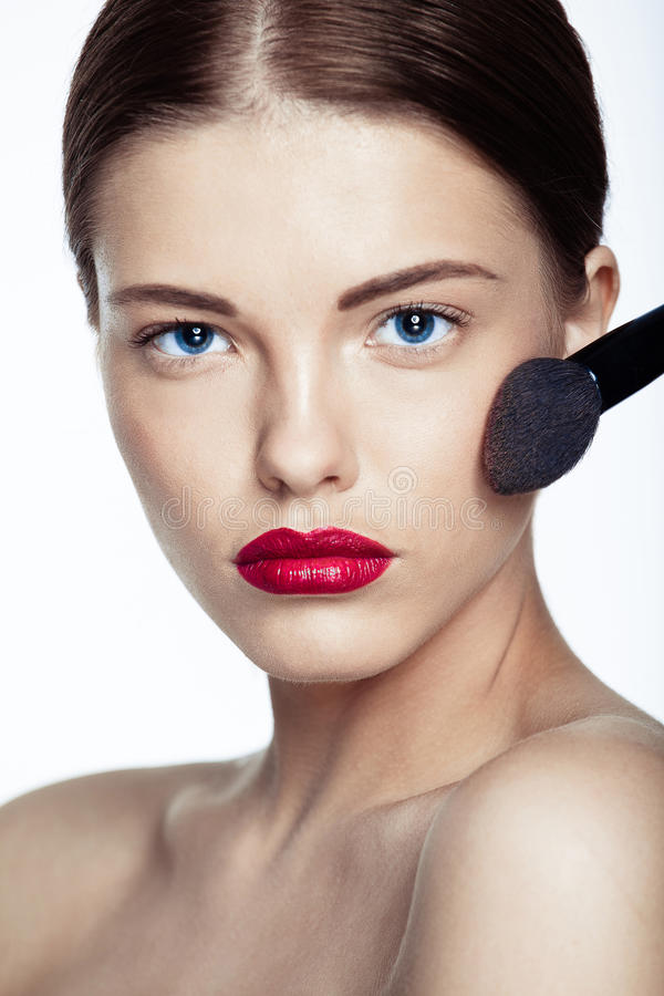 Beautiful young woman with a makeup brush. royalty free stock images