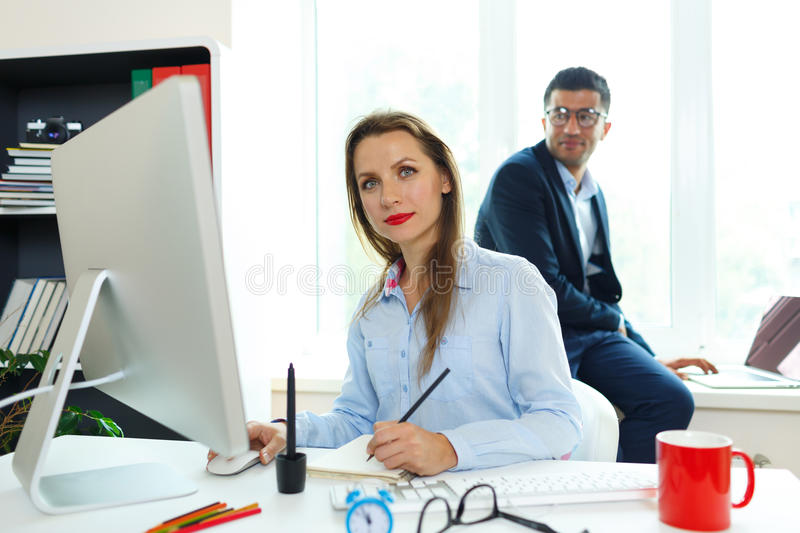 Beautiful young woman and man working from home office. Beautiful young women and men working from home office - modern business concept stock photo