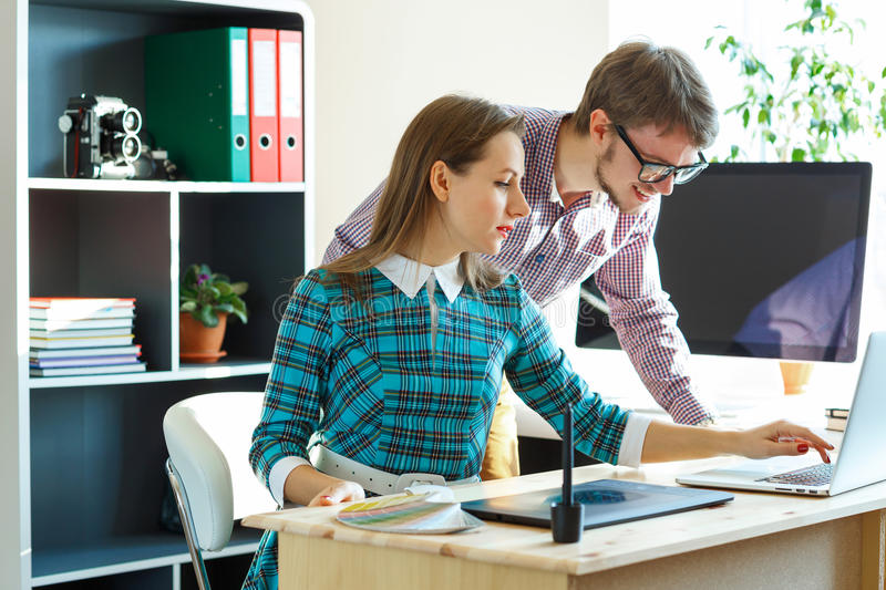 Beautiful young woman and man working from home office. Beautiful young women and men working from home office - modern business concept stock photography